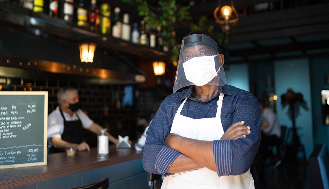 Trabajador de un restaurante usando mascarilla y pantalla facial con los brazos cruzados.
