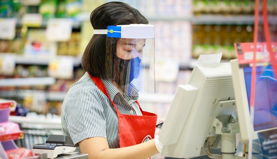 Trabajadora en la caja registradora de un almacén con mascarilla y visor protector