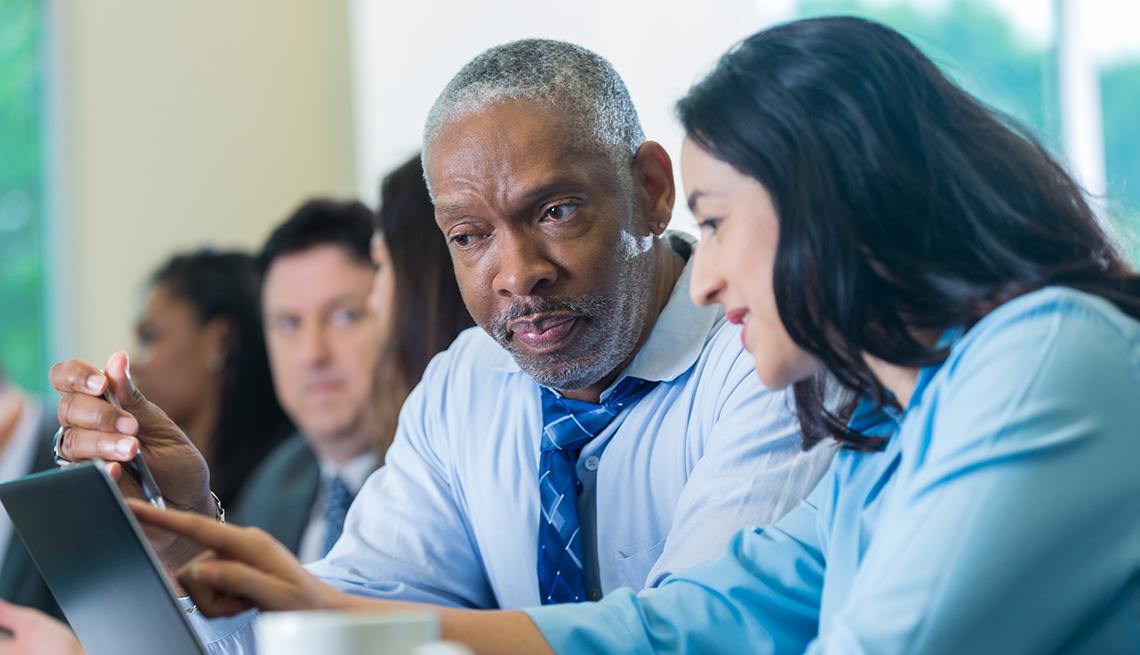 Un hombre y una mujer de diferentes edades en una oficina viendo una computadora.