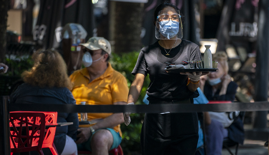 A waitress walks with a tray to a table while wearing a mask and face shield