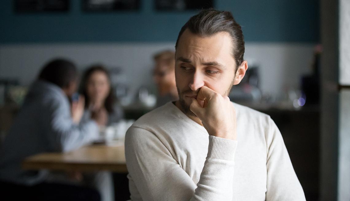 Hombre sentado en una cafetería mientras se lleva la mano a la boca y mantiene su mirada hacia abajo.
