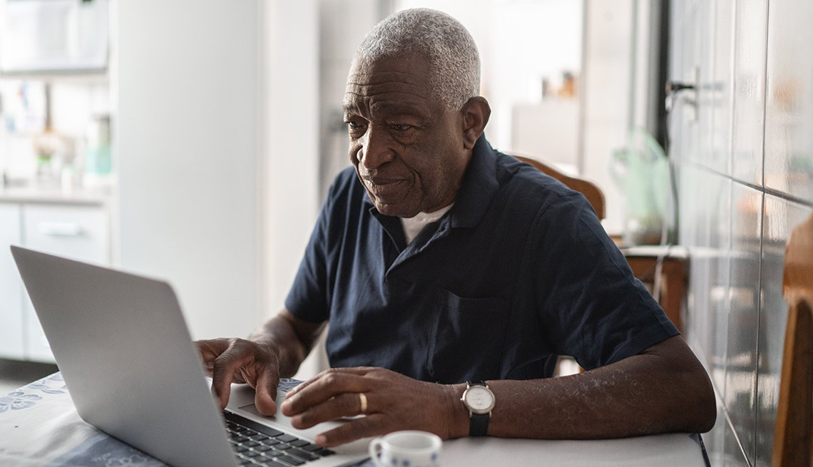 A man is working on his laptop at a table in his home