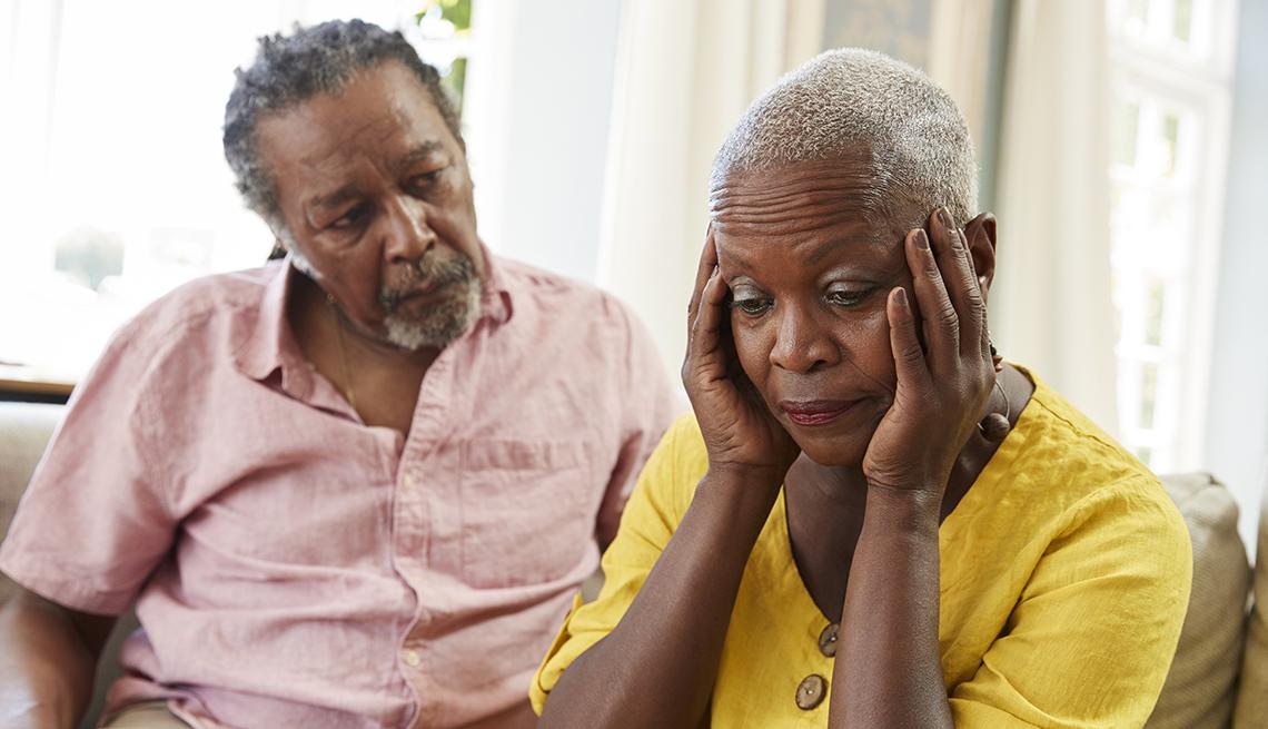 Hombre mayor sentado al lado de una mujer que se pone las manos en las sienes