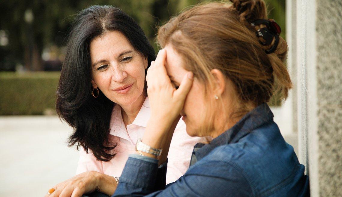 Una mujer consolando a otra que se tapa la cara con sus manos.