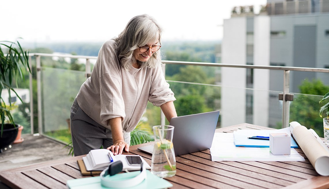 A woman standing at her desk outside on a balcony