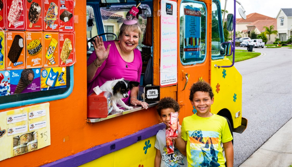 tammy hauser waves from her ice cream truck along with her dog and two kids out in front of the truck with their ice cream