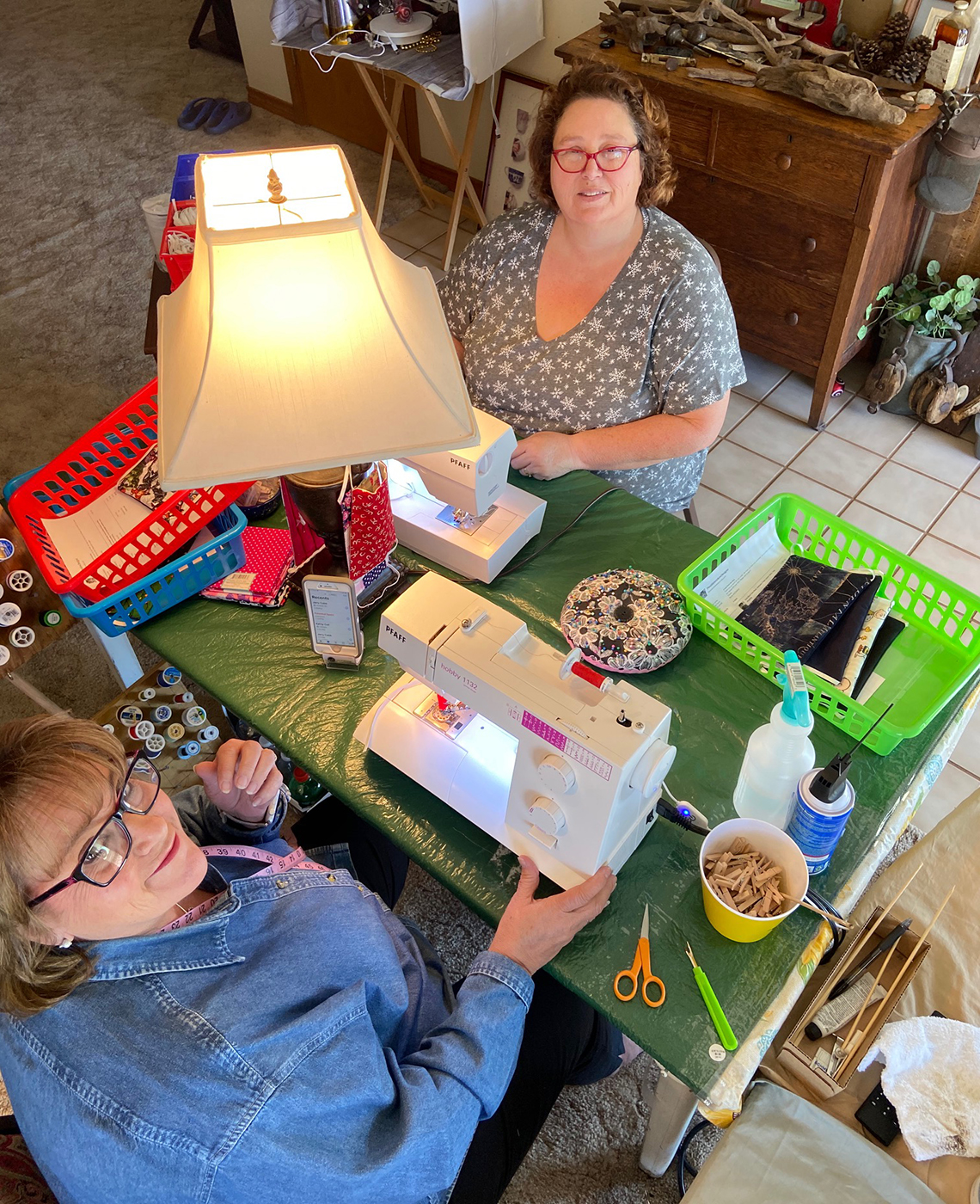 becky smith and her sister debbie cobb smile while looking up from their sewing machines