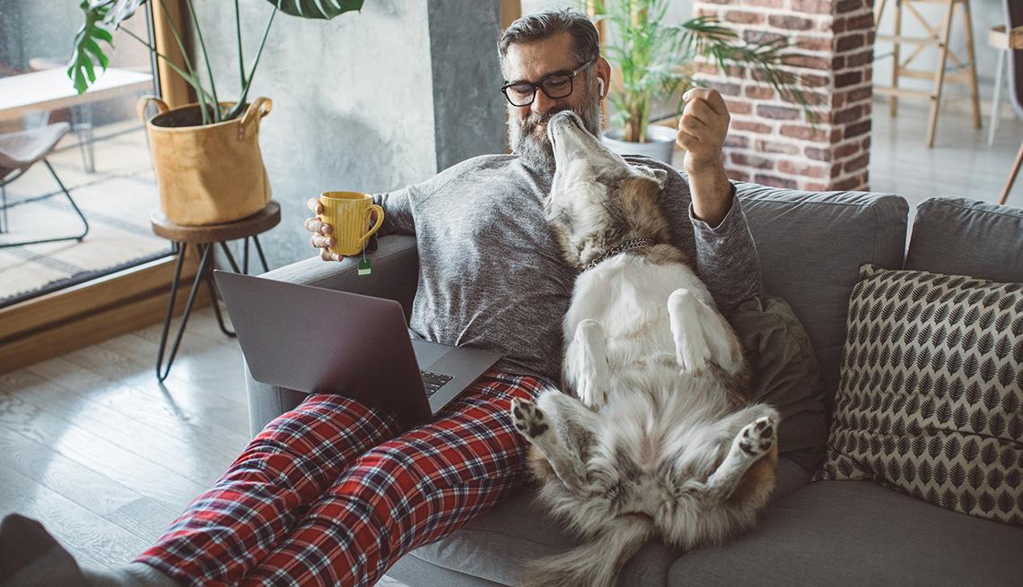Hombre en pijama sentado en el sofá de su casa con un computador en las piernas y su perro al lado