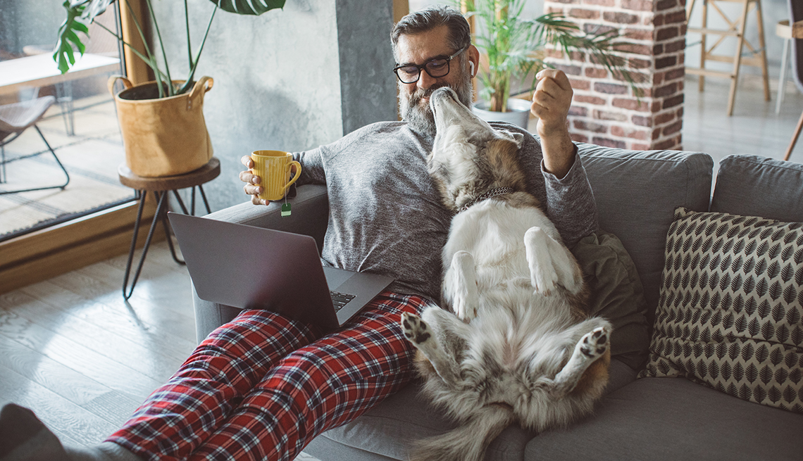 A man is sitting on the couch with his dog while working from home
