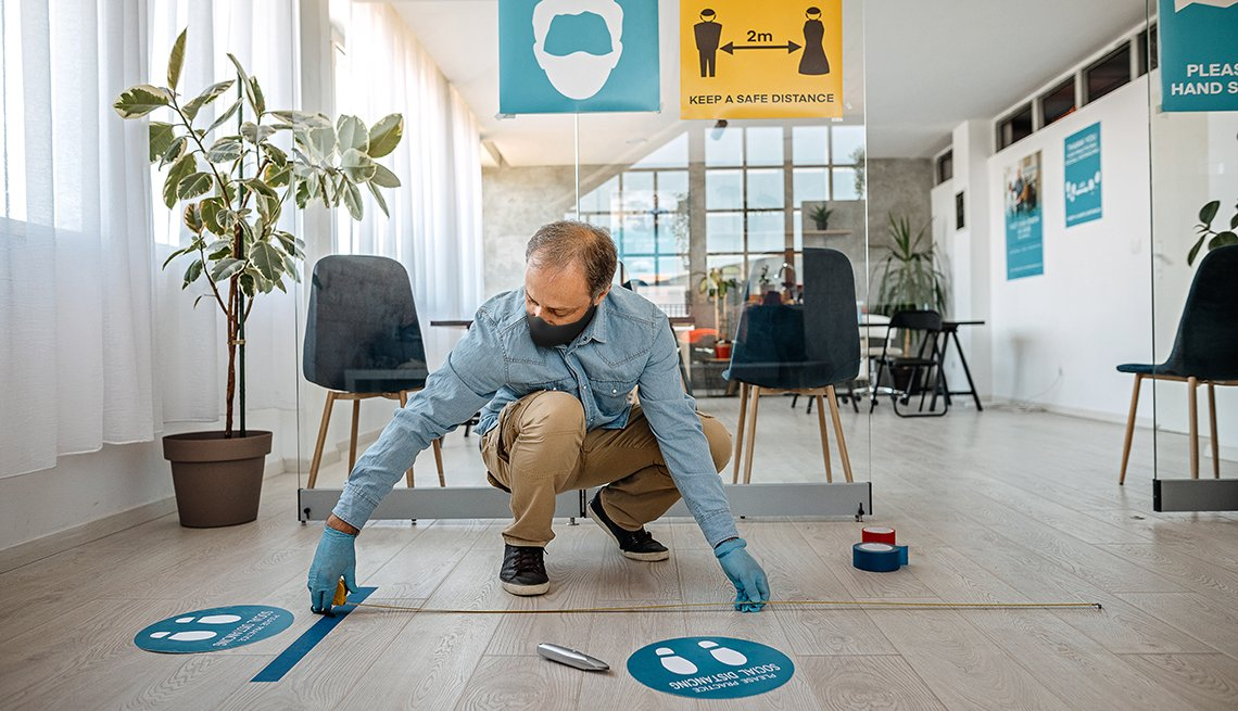 Hombre colocando señales en el piso para el distanciamiento social en una oficina.