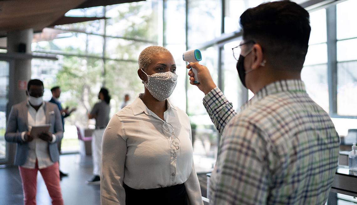 Hombre revisando la temperatura de una ejecutiva con mascarilla a la entrada de una oficina.