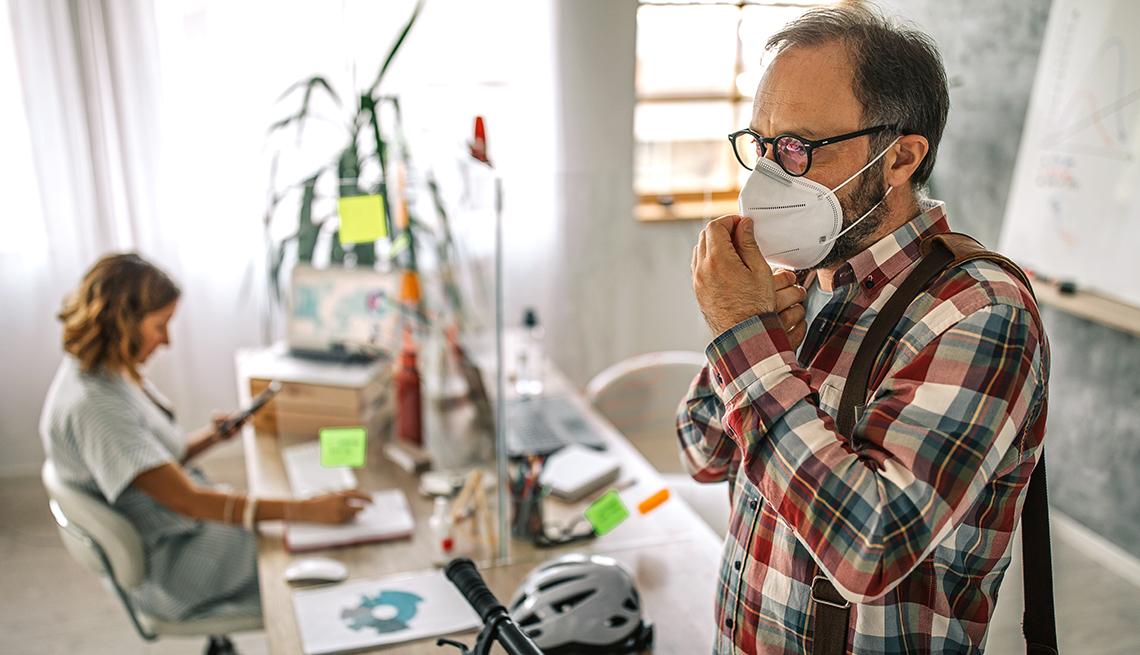 Hombre en una oficina ajustándose una mascarilla