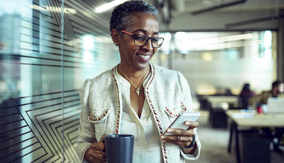 Una mujer en una oficina camina mientras mira su teléfono en una mano y en la otra lleva una taza de café