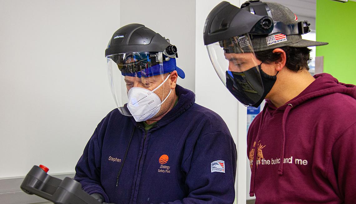 Un hombre mayor y un adolescente en un trabajo con tapabocas y protectores visuales