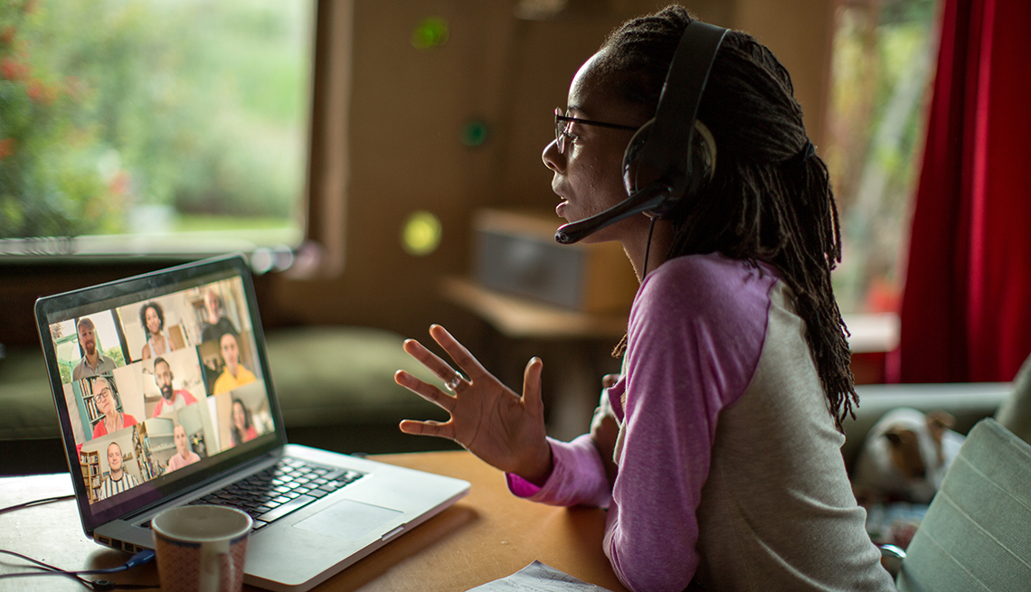 A women is working from home while talking to people on a video conference