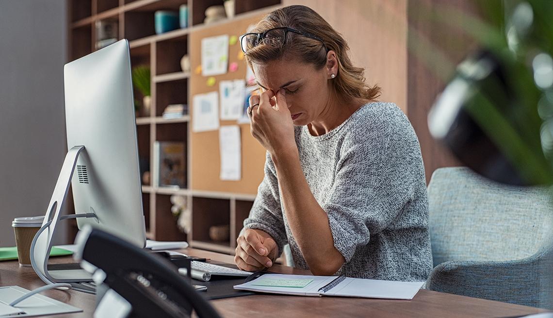 Mujer sentada frente a su computadora se toca el tabique con una mano en señal de preocupación