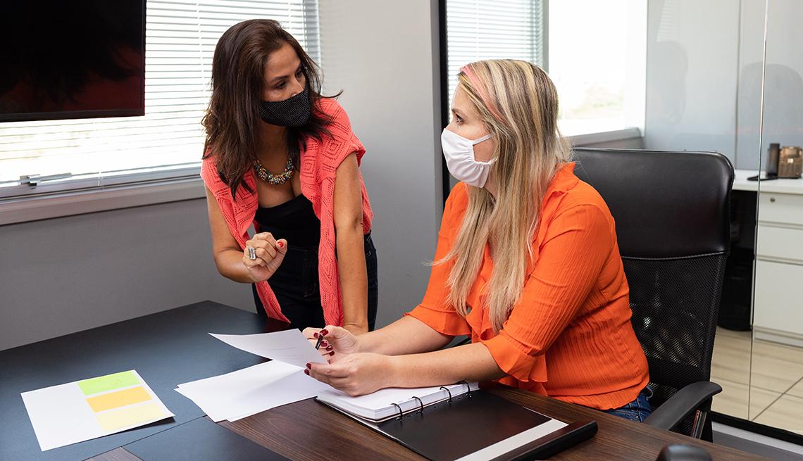 Dos mujeres usando mascarilla y hablando en una oficina