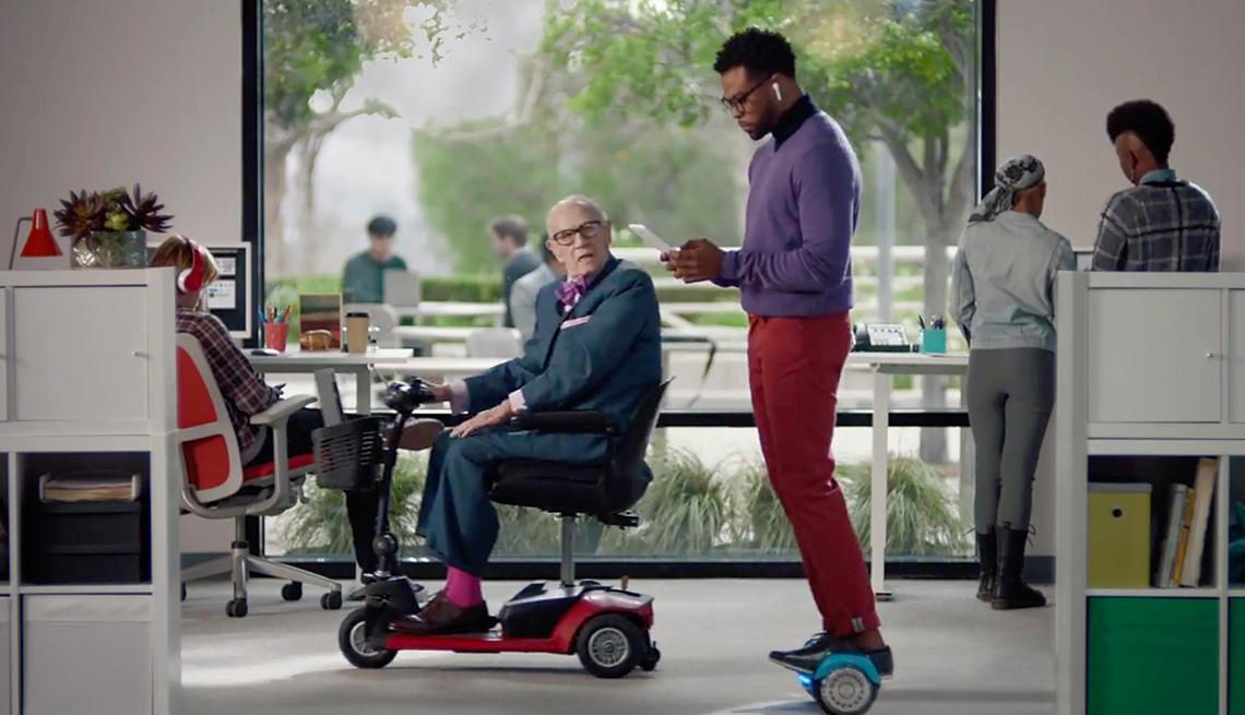 Toma de pantalla de un comercial que muestra una persona mayor en una silla eléctrica y un hombre joven en un scooter