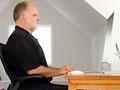 Un hombre sentado en una posición ergonómicamente correcta en el escritorio de su oficina en casa.