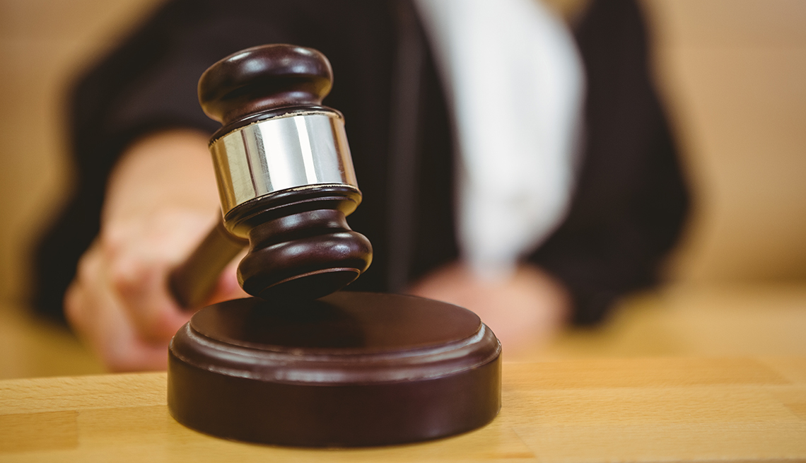 Mano de un juez colocando el martillo de la corte sobre su soporte