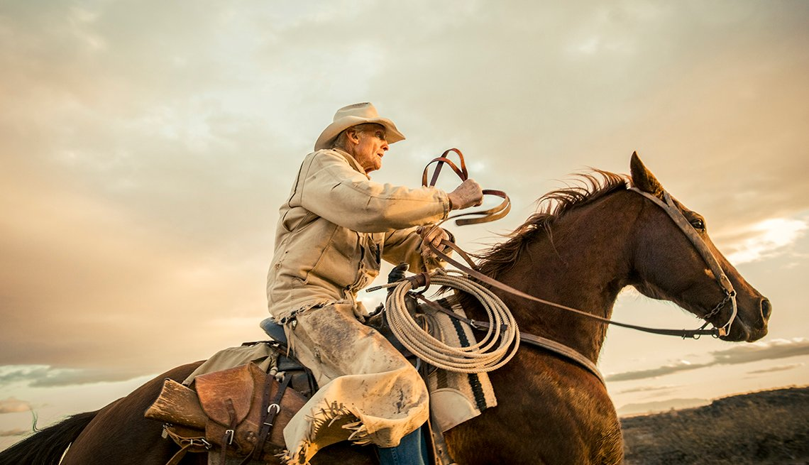 a man dressed for working on a ranch rides a horse against a pretty sky background