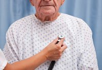Man with stethoscope pressed to his chest.