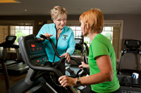 Part-time jobs for seniors who travel to warm climates in the winter- a woman helps train seniors at a fitness center in Naples, Florida