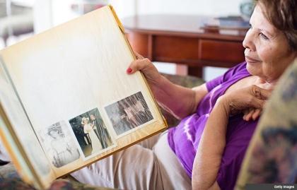 Mujer sostiene un álbum de fotos. ¿Cómo va a contar a su historia de la vida?