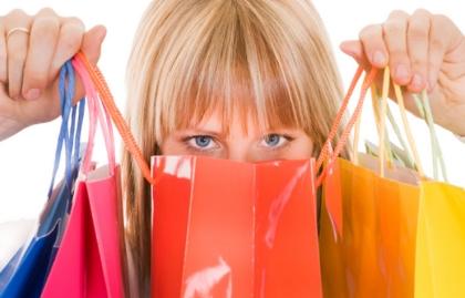 Una mujer se oculta detrás de bolsas de compras