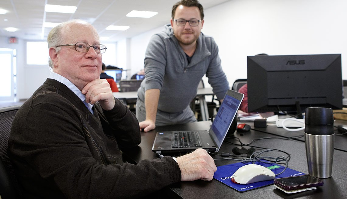 Foto de un hombre mayor y uno más joven posando a una cámara fotográfica en una oficina - Cómo triunfar en un ambiente de diversidad generacional