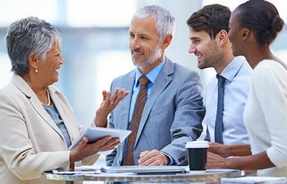 Personas en traje de ejecutivos hablando alrededor de una mesa - Metas para conseguir trabajo