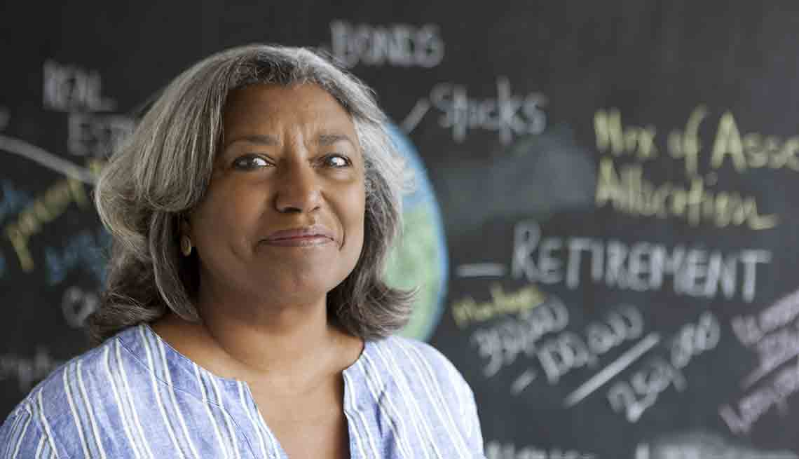 Senior Woman Smiling In Front Of Blackboard That Reads 'Retirement', Jenkins 'Saving for Your Future'