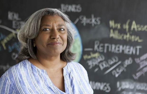 Mujer mayor sonriendo con un tablero detrás con palabras como retiro - Ahorra para el futuro