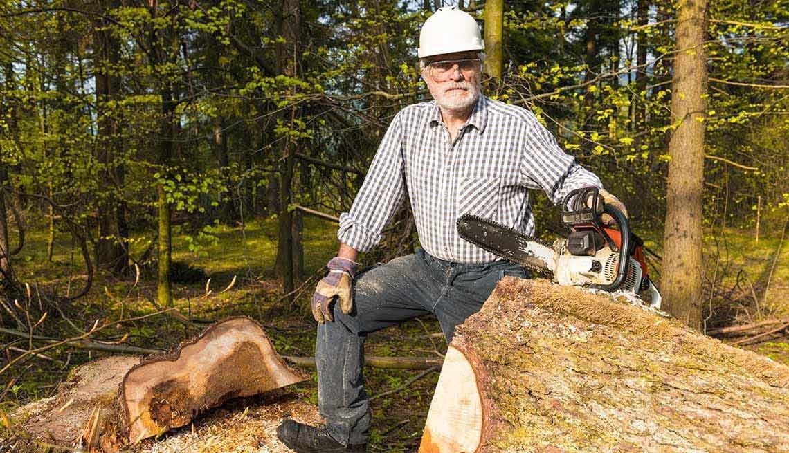 Hombre con una sierra eléctrica al lado de un tronco de árbol