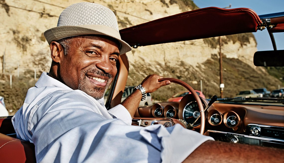 mature black man driving a car