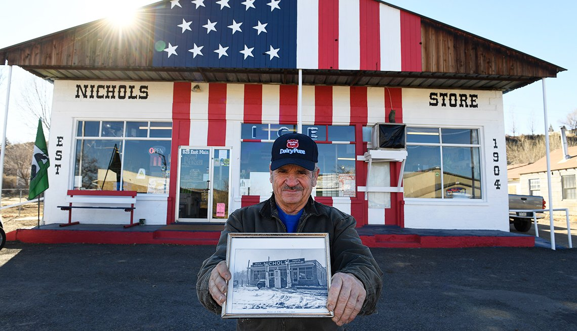 A man holds a historical photo in front of his small business