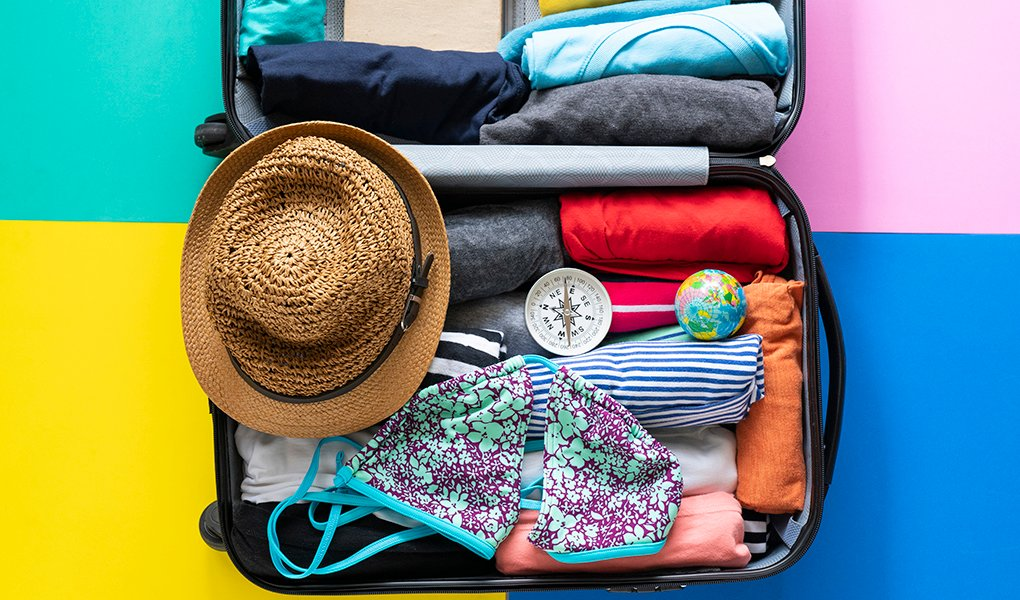 A suitcase packed tightly with a swimsuit, beach hat and compass on the top