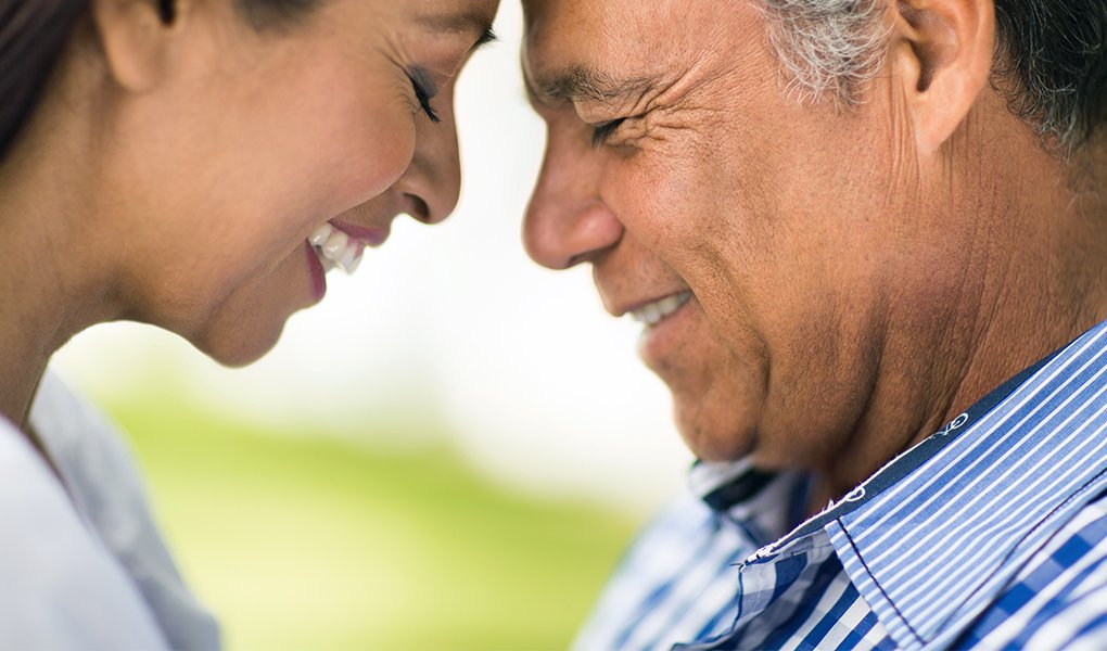 A horizontal close up shot of a mature latin couple with eyes closed, face to face and smiling.