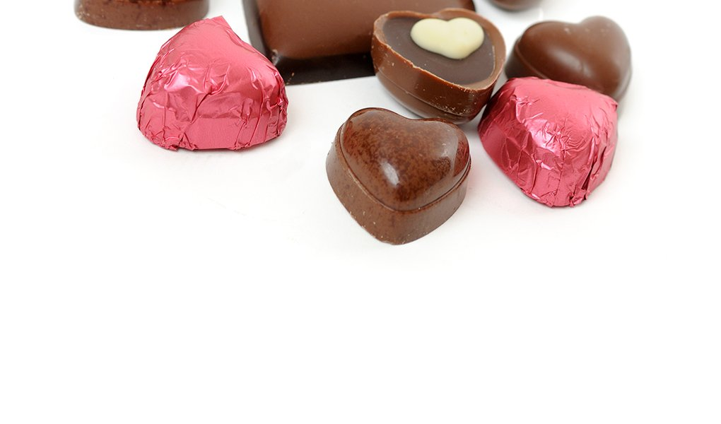 A close up of an assortment of chocolate hearts on a white background.