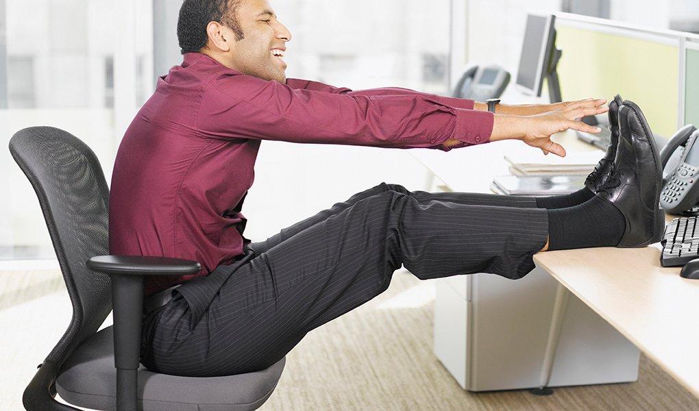 Businessman stretching at desk
