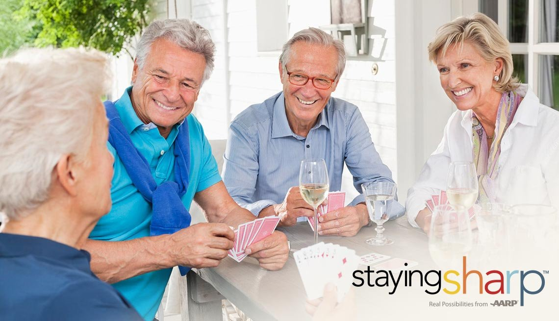 A group of people playing cards and drinking wine together