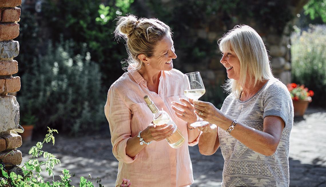 Dos mujeres maduras degustando una botella de vino blanco en sus vacaciones. Están de pie en el jardín de su Villa.
