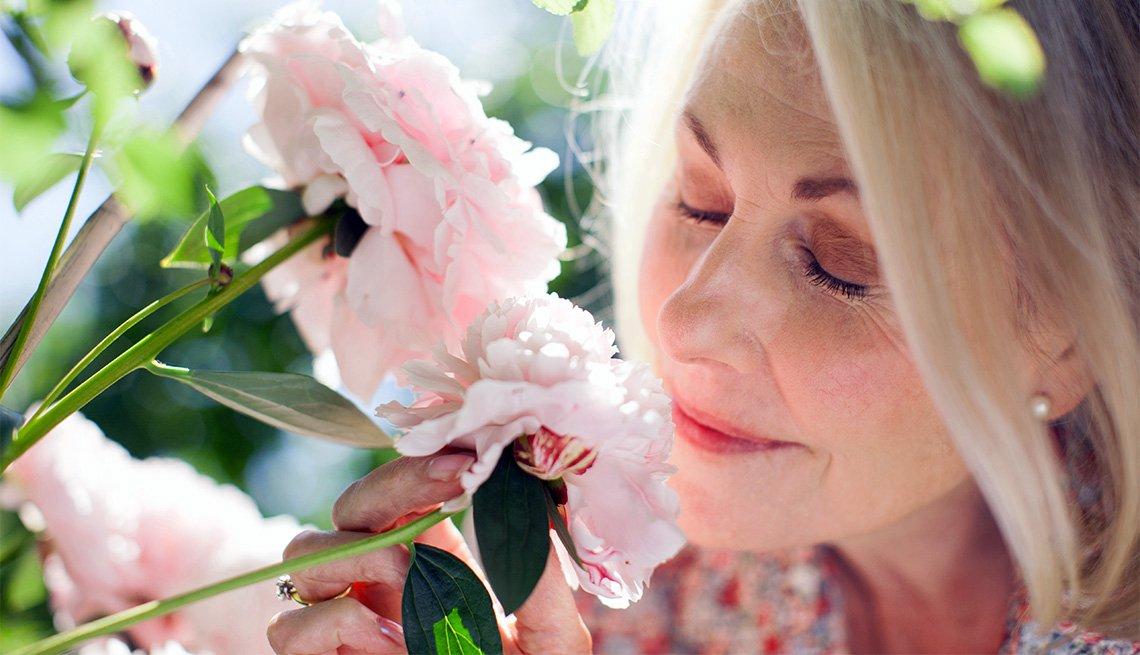 Mujer huele de cerca unas flores de color rosado