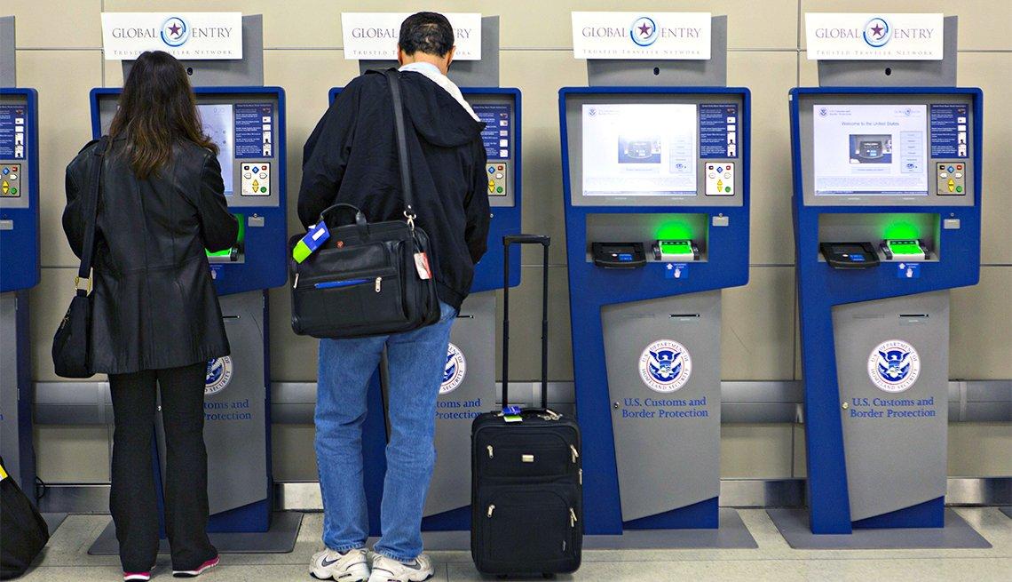 Dos personas hacen proceso inmigración en unas máquinas de un aeropuerto de Estados Unidos.