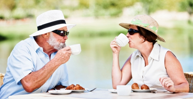 Mature couple share breakfast in the sun, The Pros and Cons of All-Inclusive Trips