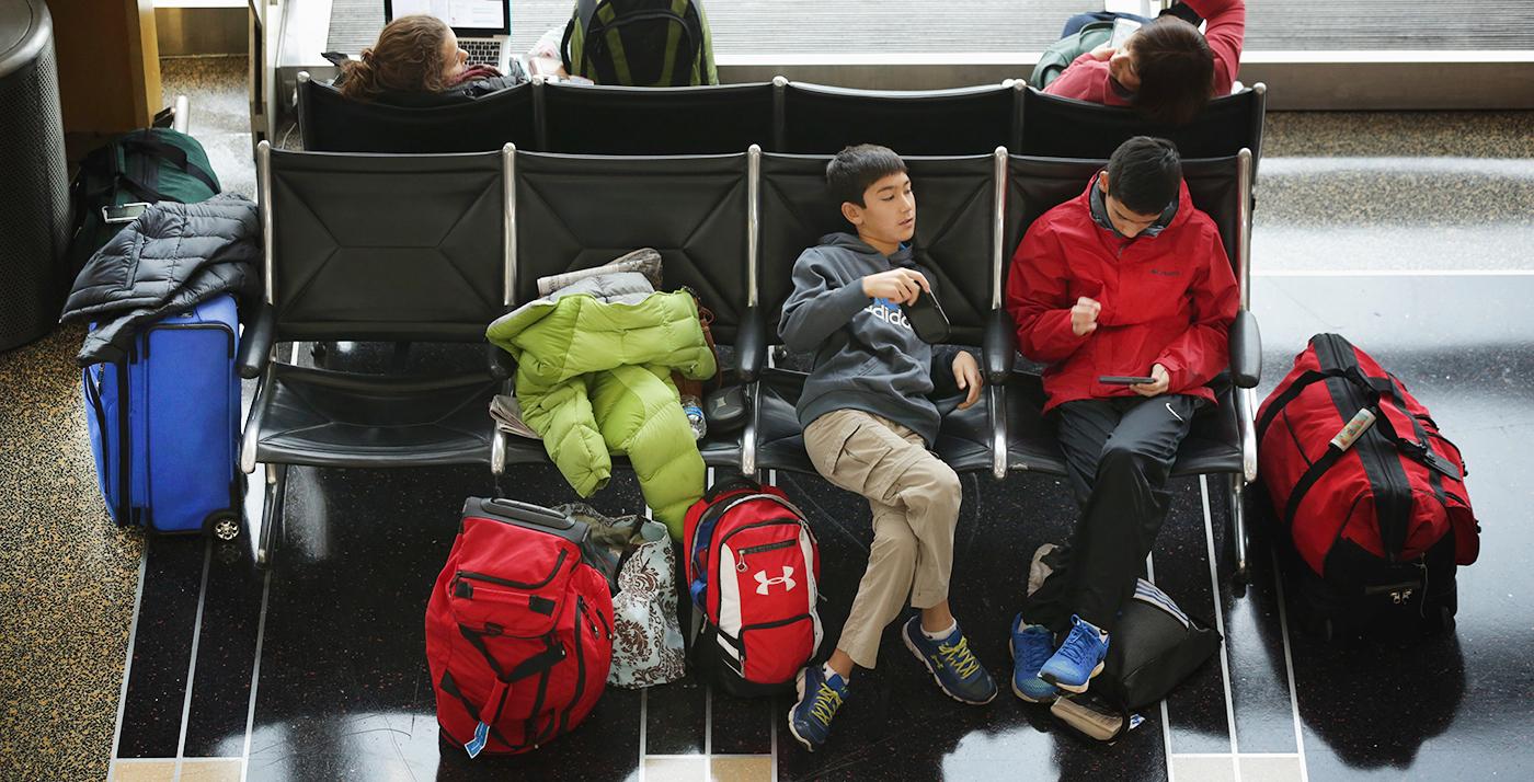 Dos jóvenes sentados y rodeados por maletas en una sala de espera de un aeropuerto.