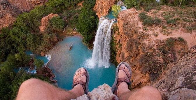 A look over a cliff at a waterfall far below between two feet. Havasu Canyon, Arizona