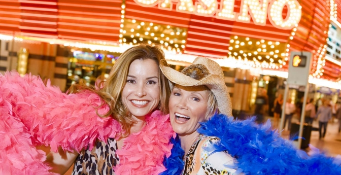 Two women wearing feather boas in front of casino.