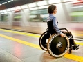 Mujer en una silla de ruedas espera el tren en la estación de metro, Sugerencias de viajes para personas con problemas de movilidad