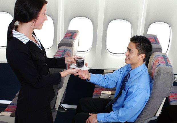 Azafata sirviendo una soda a un pasajero - Los consejos de viaje de nuestros expertos